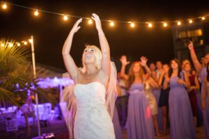 String lighting overhead at beach house wedding reception